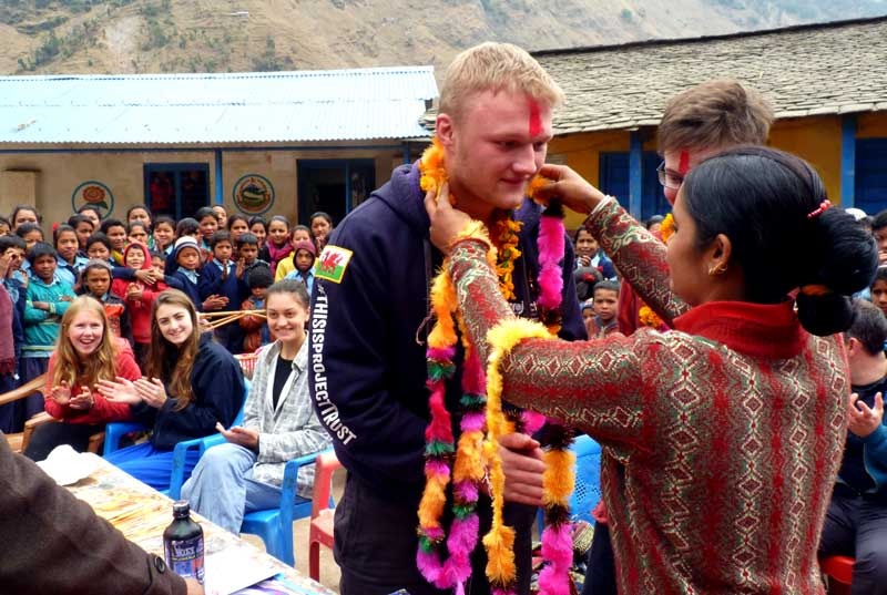 A volunteer is welcomed at local school in Nepal (Image projecttrust.org.uk)